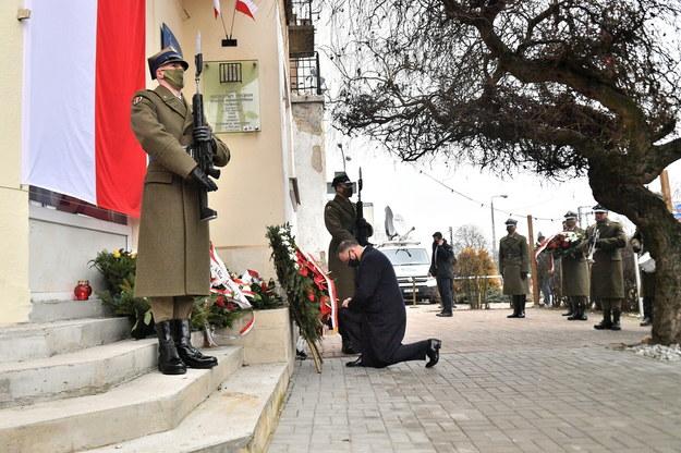 """Prezydent RP Andrzej Duda (C) składa wieniec przed tablicą upamiętniającą ofiary komunistycznego terroru w miejscu pamięci """"Willa Jasny Dom"""" w Warszawie /Andrzej Lange /PAP"""