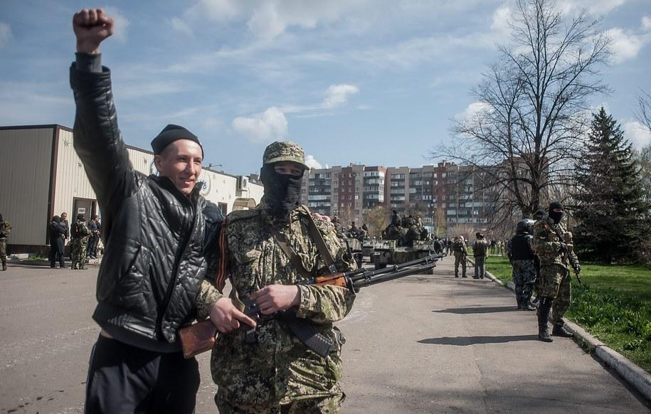 Prorosyjski aktywista pozuje do zdjęcia z uzbrojonym mężczyzną w Słowiańsku w obwodzie donieckim /ROMAN PILIPEY /PAP/EPA