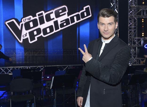 "Prowadzący program Tomasz Kammel na tle loga ""The Voice of Poland"" /AKPA"