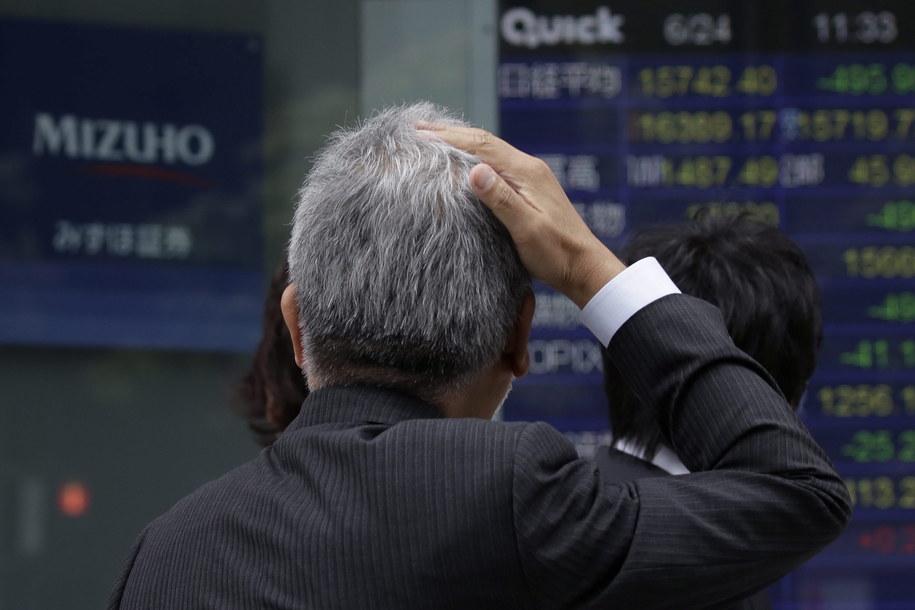 Przechodzień przed monitorem wyświetlającym dane z giełdy w Tokio /Kiyoshi Ota /PAP/EPA