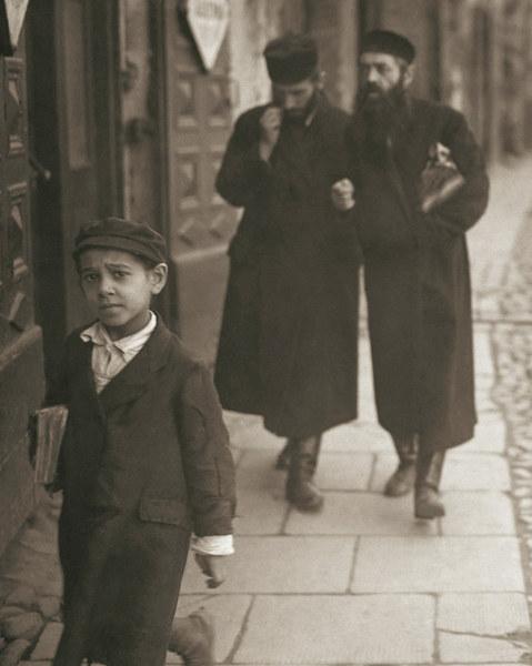 Mały chłopiec wchodzący do bramy domu przy ul. Świętojerskiej 5 wraca z zajęć w chederze, trzymając pod pachą książkę. Za jego plecami przechadza się para studentów jesziwy, z powagą dyskutujących na tematy talmudyczne.