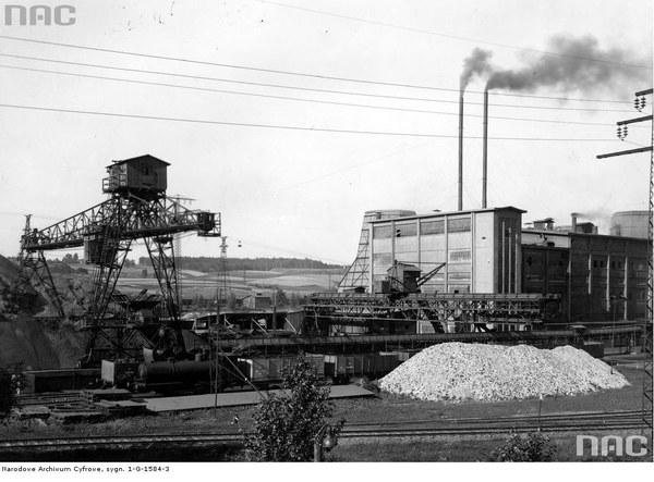 """Zakłady """"Elektro"""" w Łaziskach Górnych. Widok ogólny - na pierwszym planie bocznica kolejowa z pociągiem prowadzonym przez parowóz bezogniowy. Widoczna również suwnica, budynek zakładu i linia wysokiego napięcia"""