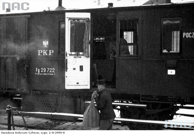 Przewóz poczty. Mężczyzna z workiem pocztowym stoi przed wagonem pocztowym na peronie, 1931 /Z archiwum Narodowego Archiwum Cyfrowego