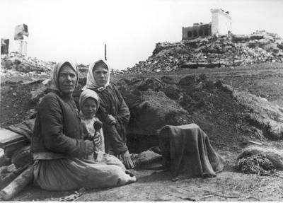 Radziecka kobieta z dziećmi przed wykopaną w ziemi jamą służącą za mieszkanie. W tle widoczna spalona wieś. /Ze zbiorów Narodowego Archiwum Cyfrowego