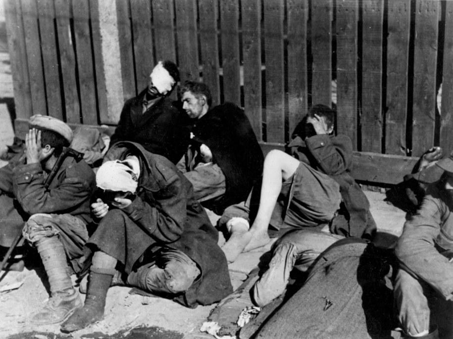Ranni powstańcy odpoczywają przy płocie na Krakowskim Przedmieściu. Wrzesień 1944 roku. /CTK /PAP