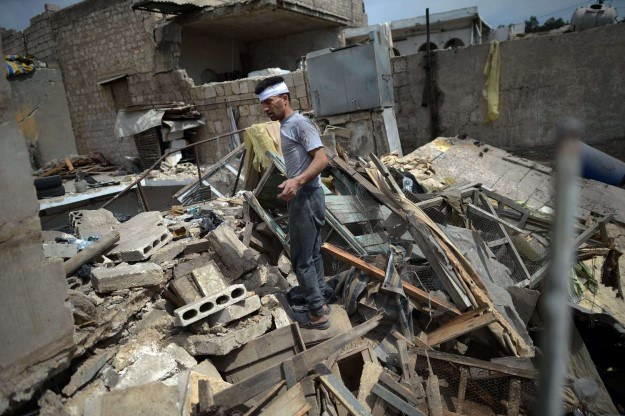 Ranny mężczyzna na gruzach własnego domu (Aleppo) /AFP
