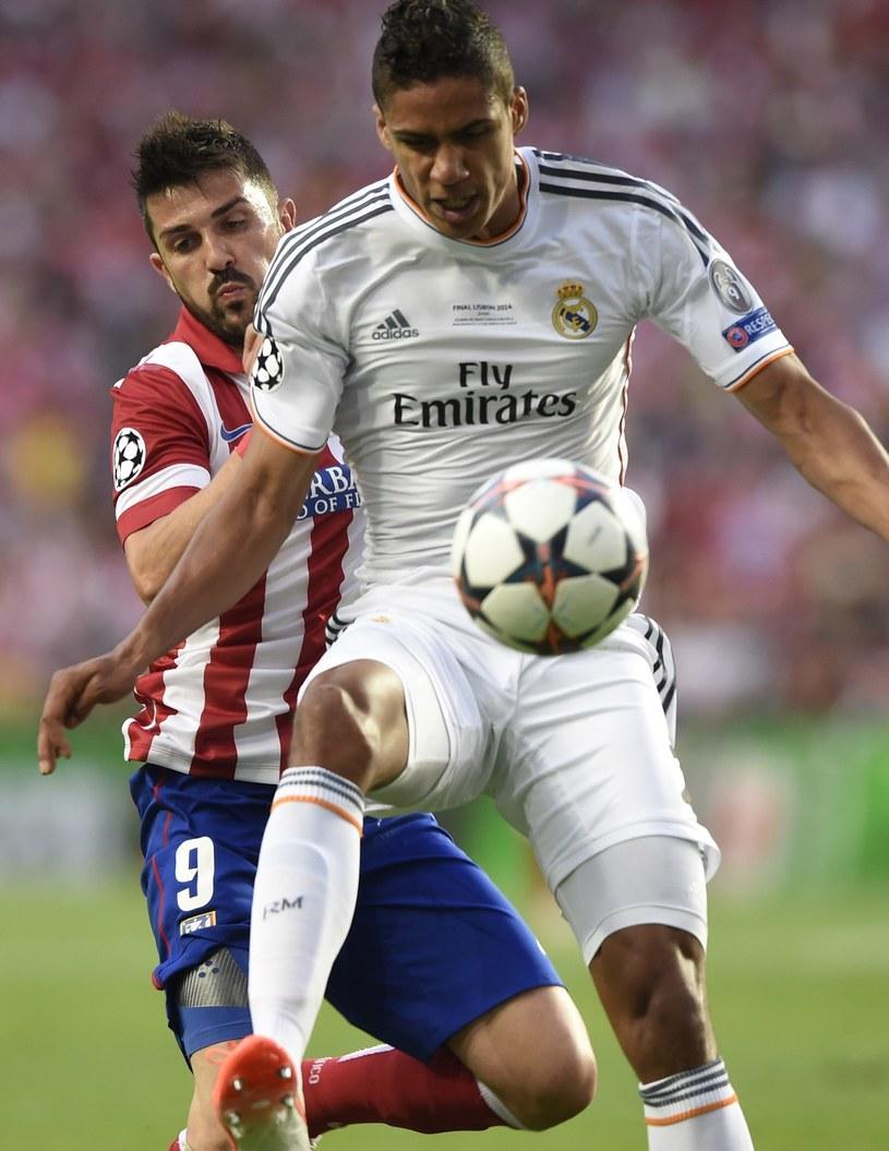 Raphael Varane walczy o piłkę z Davidem Villą /AFP