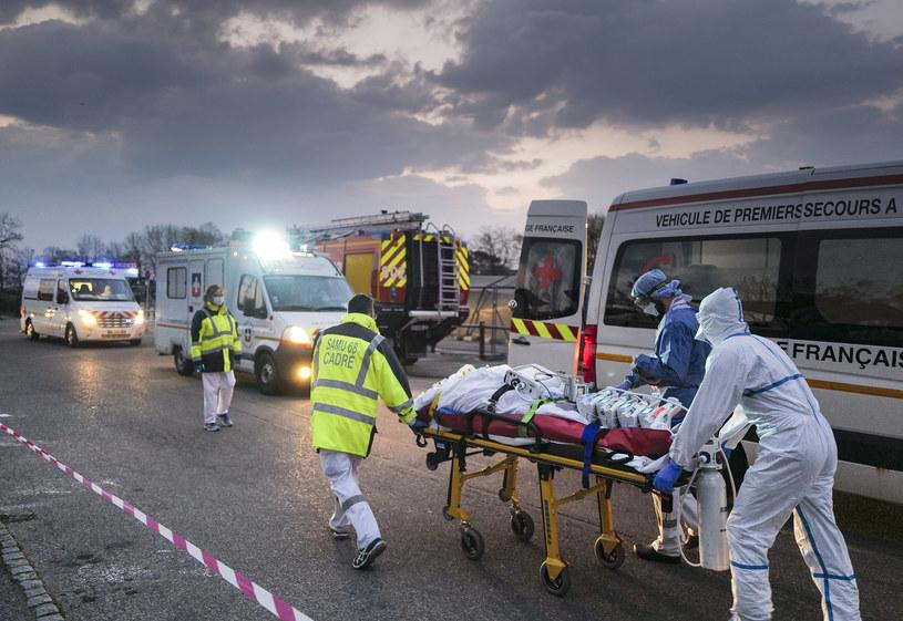 Ratownicy medyczni we Francji przewożą pacjenta z koronawirusem, zdj. ilustracyjne /SEBASTIEN BOZON /AFP