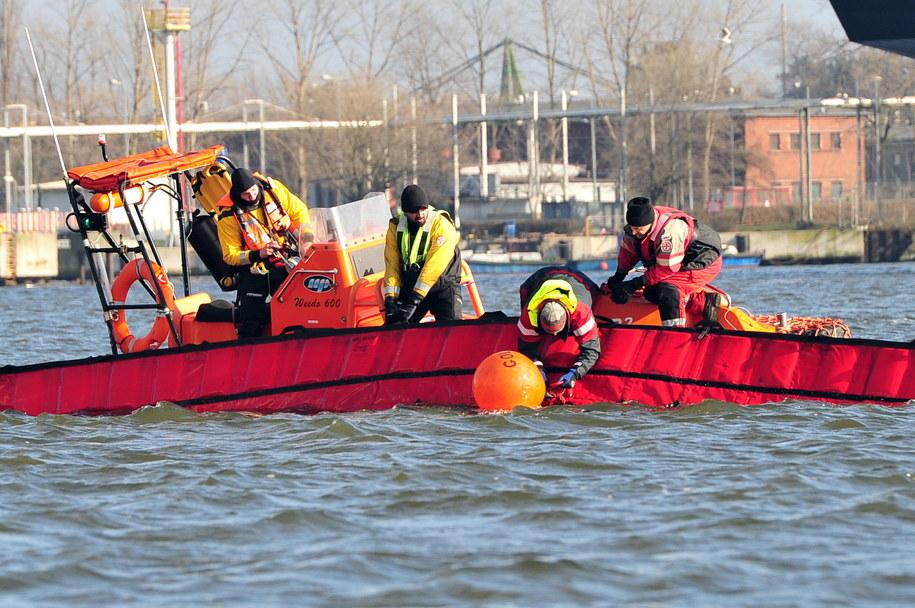 Ratownicy morscy prowadzą akcję neutralizacji paliwa, które wyciekło z holownika Kuguar spoczywającego na dnie kanału w świnoujskim porcie /Marcin Bielecki /PAP