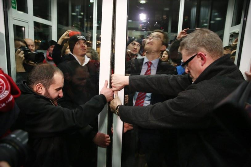 Reżyser Grzegorz Braun (P) z grupą osób okupujących siedzibę PKW otwiera na siłę drzwi do siedziby komisji, aby umożliwić wtargnięcie kolejnym demonstrantom /Tomasz Gzell /PAP