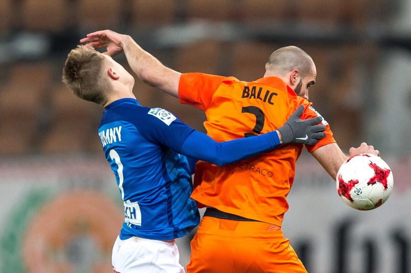 Robert Gumny (z lewej) w walce o piłkę z Saszą Baliciem /Fot. Maciej Kulczyński /PAP