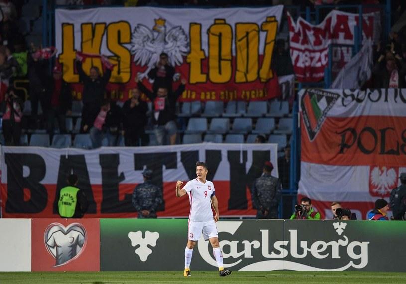 Robert Lewandowski cieszy się z gola w meczu z Armenią. W tle trybuna z polskimi kibicami /AFP
