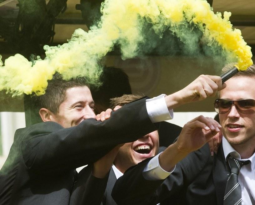 Robert Lewandowski pali racę w kolorach Borussii Dortmund podczas mistrzowskiej fety z maja 2011 roku. Z prawej: Marco Stiepermann. /AFP