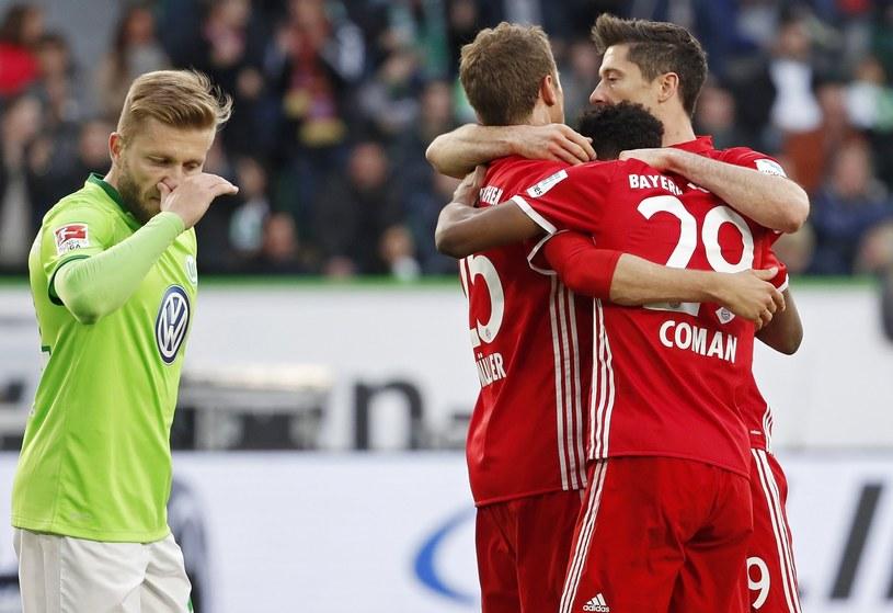 Robert Lewandowski świętuje strzeloną bramkę. Z lewej pomocnik Wolfsburga Jakub Błaszczykowski /PAP /