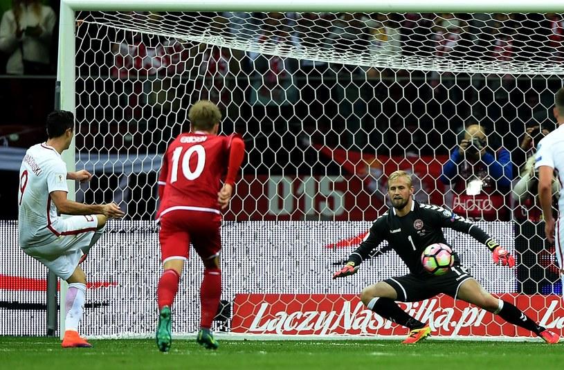 Robert Lewandowski uderza na duńską bramkę z rzutu karnego /AFP