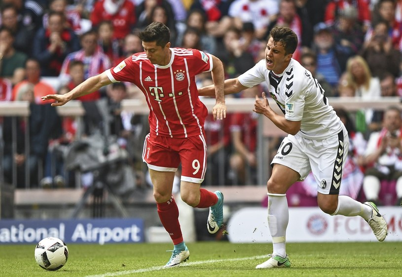 Robert Lewandowski w meczu z Freiburgiem. Z prawej Marc-Oliver Kempf. /PAP/EPA
