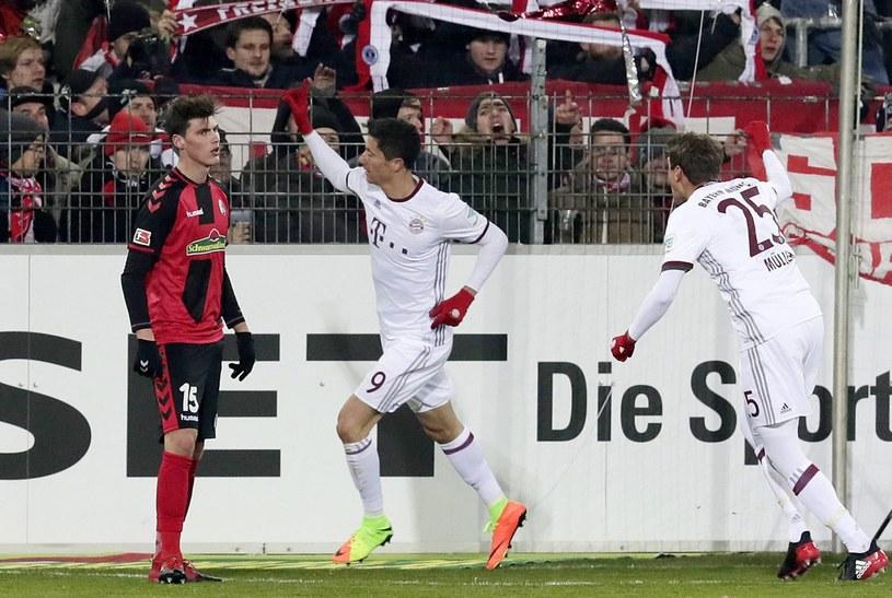 Robert Lewandowski (w środku) cieszy się z gola /AFP