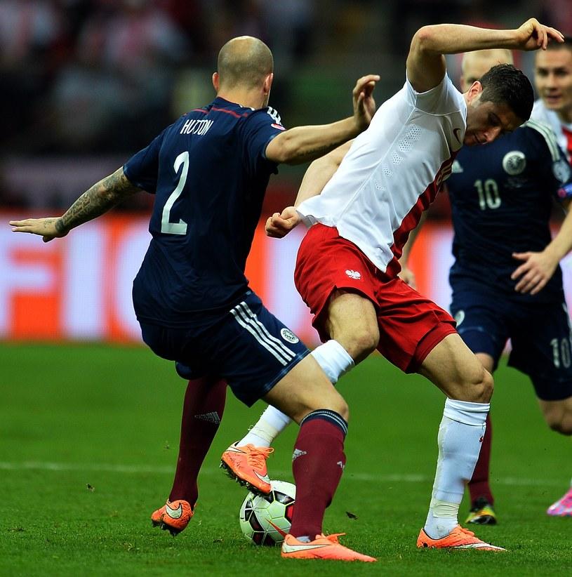 Robert Lewandowski w starciu z Alanem Huttonem podczas meczu Polska - Szkocja. /AFP