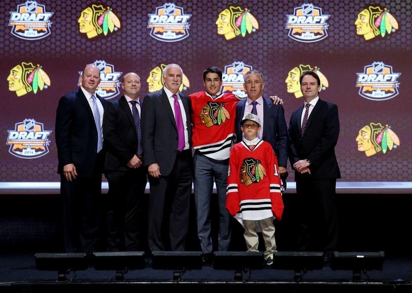 Rodzina NHL rośnie w siłę. Na zdjęciu w środku Nick Schmaltz, który został wybrany jako 20 zawodnik przez Chicago Blackhawks w I rundzie draftu NHL 2014. /AFP