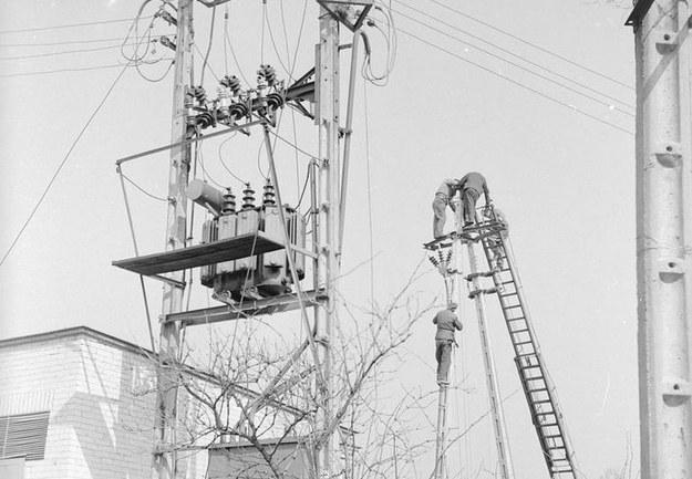 Rolnicza Spółdzielnia Produkcyjna w Dawidach. race elektryfikacyjne. Mężczyźni w czasie robót na betonowym słupie /Z archiwum Narodowego Archiwum Cyfrowego