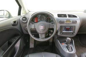 Seat Leon II: Sportowa pozycja za kierownicą. Dobra jakość wykończenia, ale materiały – przeciętne. Na konsoli opcjonalny duży ekran multimedialny – ożywia nieco tę dużą połać plastiku. /Motor