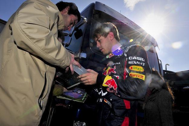 Sebastian Vettel (z prawej) rozdaje autografy /AFP