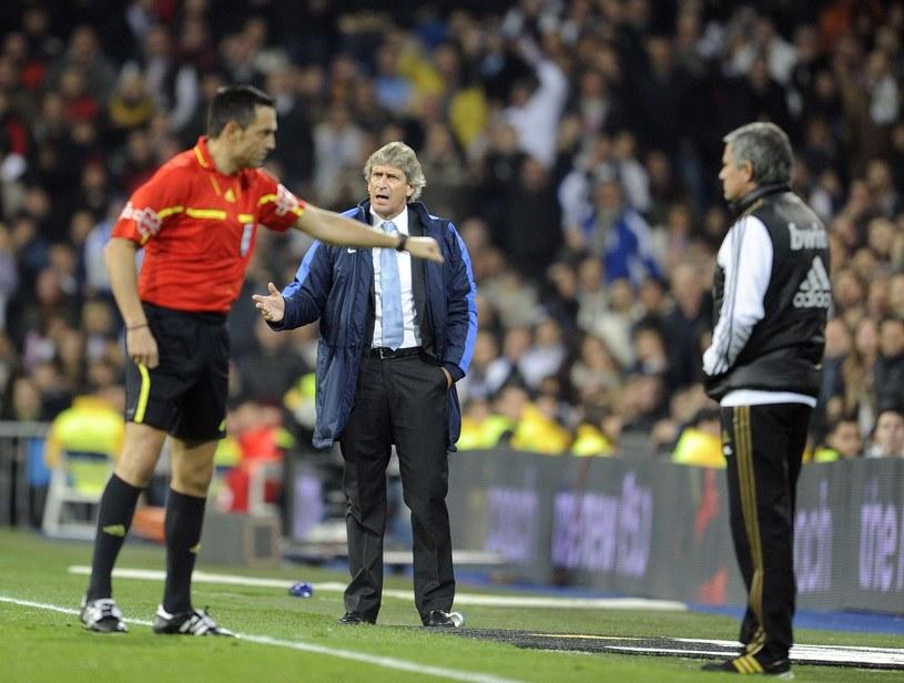 Sędzia Teixeira Vitienes przywołuje do porządku Jose Mourinho podczas meczu Realu z Malagą (z tyłu jej trener Manuel Pellegrini). /AFP