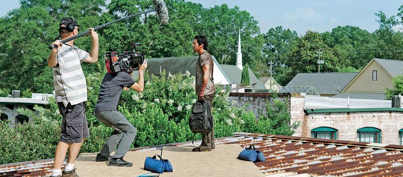 Serialowy Glenn (Steven Yeun) podczas kręcenia jednej ze scen nowego sezonu. Finał tego odcinka postawił pytanie: czy Glenn zginął? Na szczęście, przeżył. W tle widać wieżę kościoła... /Świat Seriali