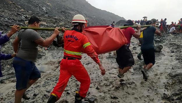 Służby niosą ciało jednej z ofiar /PAP/EPA