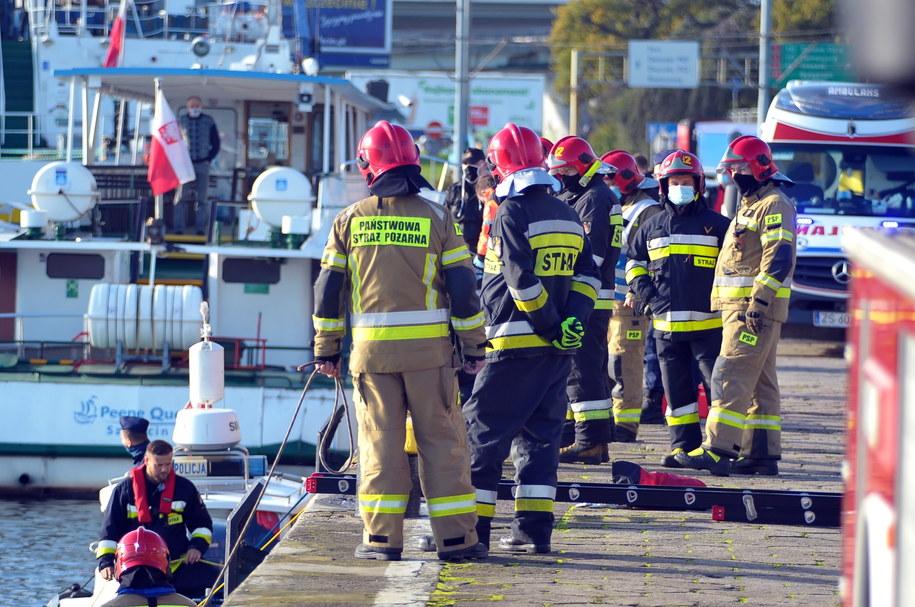 Służby pracują na miejscu wypadku przy ulicy Jana z Kolna w Szczecinie, gdzie samochód osobowy wjechał do Odry / Marcin Bielecki    /PAP