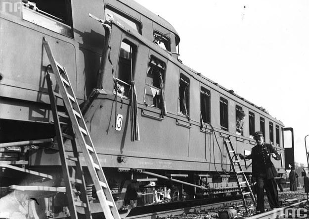 Spiętrzone wagony po katastrofie kolejowej w Krzeszowicach. Widoczne drabiny przystawione do okien i kolejarz trzymając przewody gazowe do palników /Z archiwum Narodowego Archiwum Cyfrowego