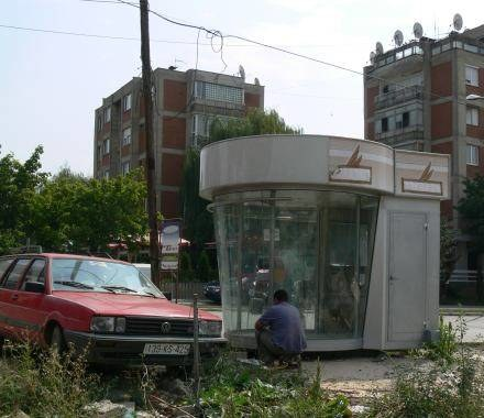 Sprzedawca siedzi przed kioskiem w centrum Prisztiny. Nowy design gryzie się z otoczeniem /INTERIA.PL