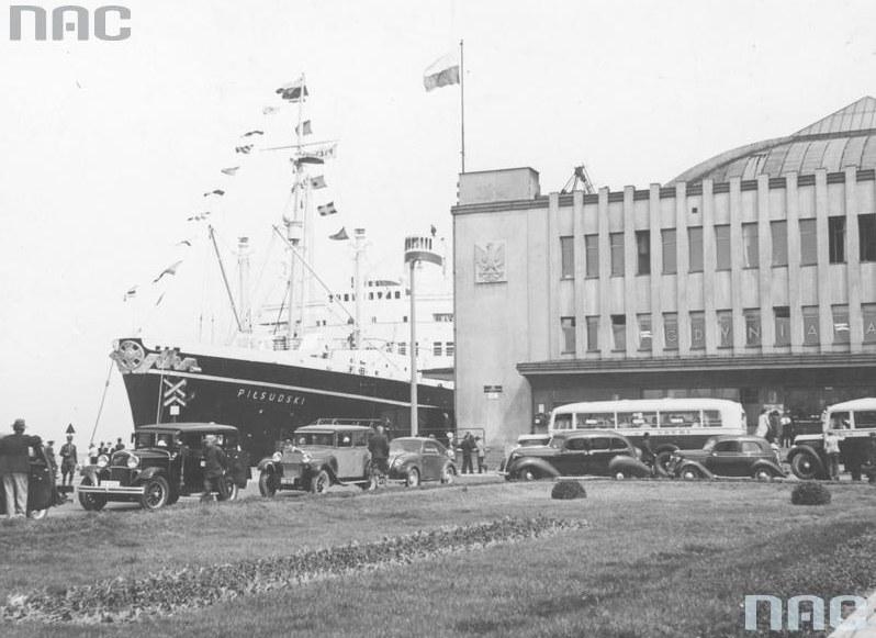 """Statek pasażerski """"Piłsudski"""" w porcie gdyńskim w gali flagowej cumujący przy nabrzeżu francuskim. Widoczny fragment budynku Dworca Morskiego /Z archiwum Narodowego Archiwum Cyfrowego"""