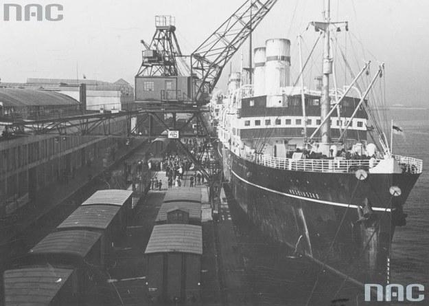 """Statek pasażerski SS """"Kościuszko"""" widoczny od strony dziobu podczas przeładunku w porcie w Gdyni. Widoczne portowe urządzenia przeładunkowe oraz wagony kolejowe /Z archiwum Narodowego Archiwum Cyfrowego"""