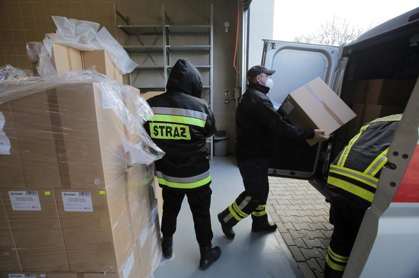 Strażacy-ochotnicy podczas załadunku maseczek ochronnych w Olsztynie /Tomasz Waszczuk /PAP