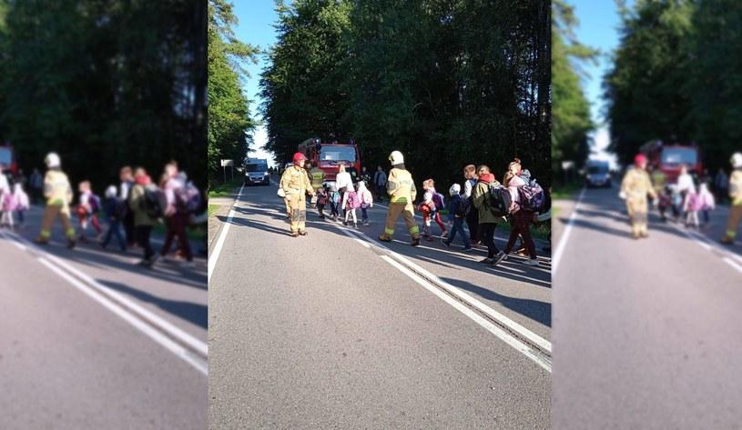 Strażacy przeprowadzają dzieci przez jezdnie po wypadku autokaru z udziałem pijanego kierowcy /KW PSP Gdańsk /materiały prasowe