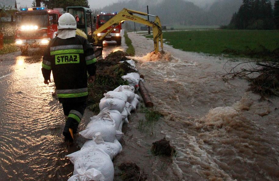 Strażacy układają worki z piaskiem, zabezpieczając zalaną drogę w rejonie Witowa /Grzegorz Momot /PAP
