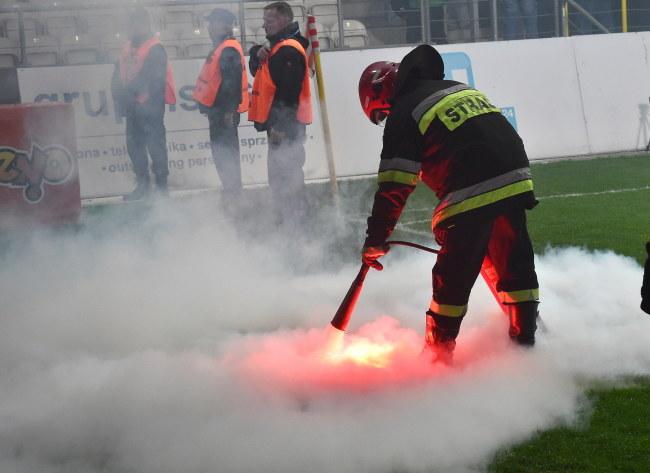 Strażak gasi race na boisku podczas meczu: Cracovia - Pogoń Szczecin /Jacek Bednarczyk /PAP