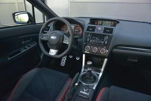 Subaru WRX STI ST000: w stosunku do modelu starszej generacji, w górnej części deski rozdzielczej pojawiło się miękkie tworzywo. Na konsoli środkowej króluje imitacja włókna węglowego. Obsługa jest łatwa. /Motor