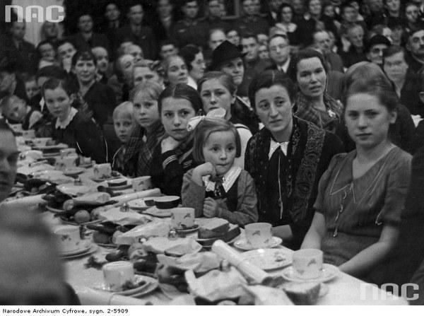 Obchody Bożego Narodzenia przez volksdeutschów w Starym Teatrze. Rodzice z dziećmi siedzą przy zastawionym stole, grudzień 1939