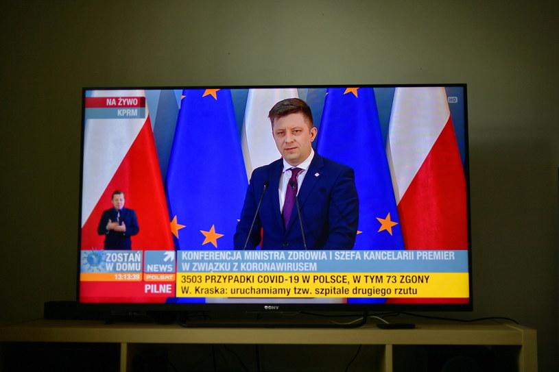 szef Kancelarii Prezesa Rady Ministrów Michał Dworczyk (na ekranie telewizora) podczas konferencji prasowej / Marcin Obara  /PAP