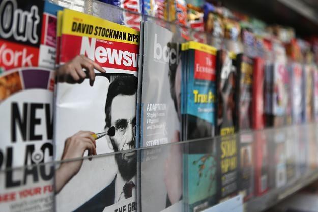 Szeleszczące gazety nigdy nie znikną, lecz wiele przenosi się do internetu /AFP