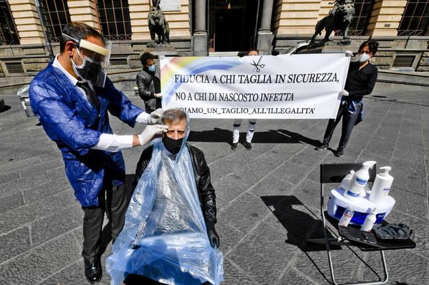 """Szyld: """"Ufaj tym, którzy tną bezpiecznie, a nie tym, którzy potajemnie zarażają"""" /CIRO FUSCO /PAP/EPA"""