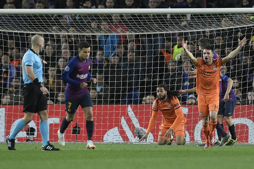 Szymon Marciniak dyktuje karnego dla Barcy, choć to Luis Suarez faulował. Na nic się zdadzą protesty obrońcy OL  Leo Duboisa i oglądanie powtórek VAR. /AFP