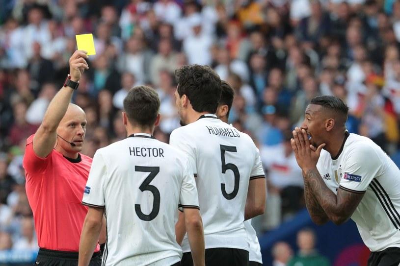 Szymon Marciniak pokazuje żółtą kartkę Matsowi Hummelsowi z reprezentacji Niemiec. /AFP