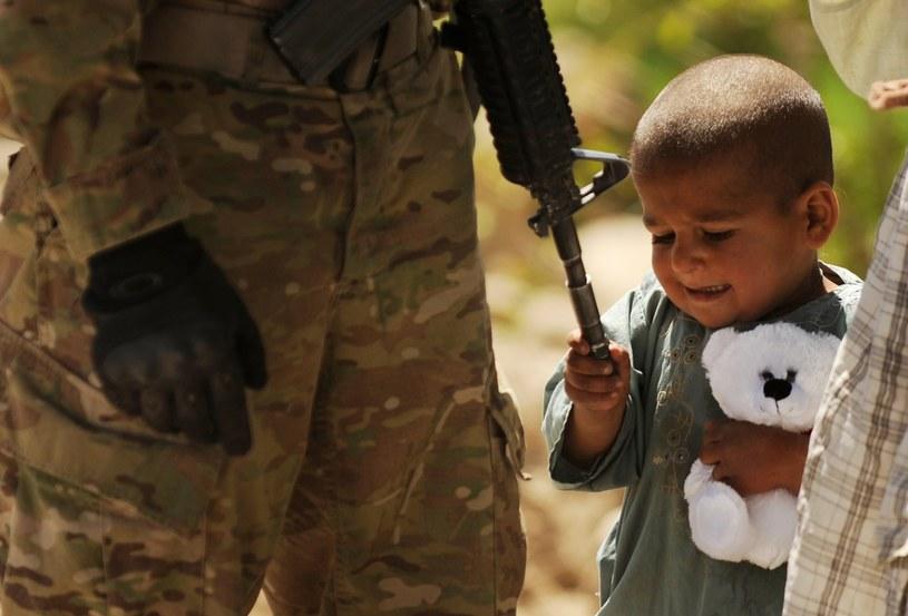 Tarok Kolache, prowincja Kandaha. Afgański chłopiec z misiem bawi się lufą karabinu żołnierza /AFP