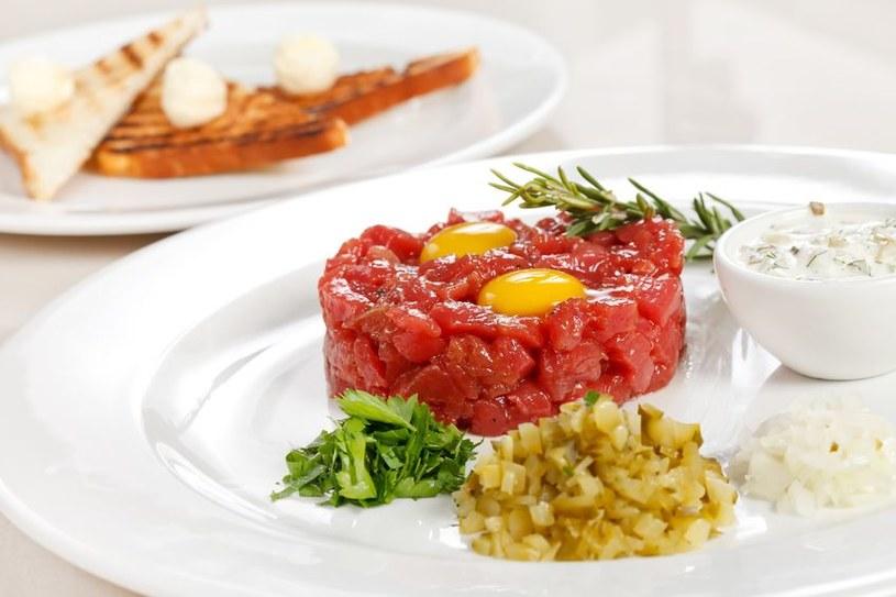 Tatara podaj z surowym jajkiem. Dodatki, np. kiszone ogórki lub cebulkę, ułóż osobno na talerzu /123RF/PICSEL