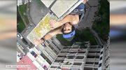 Ten miłośnik mocnych wrażeń robi pompki, zwisając z dachu budynku