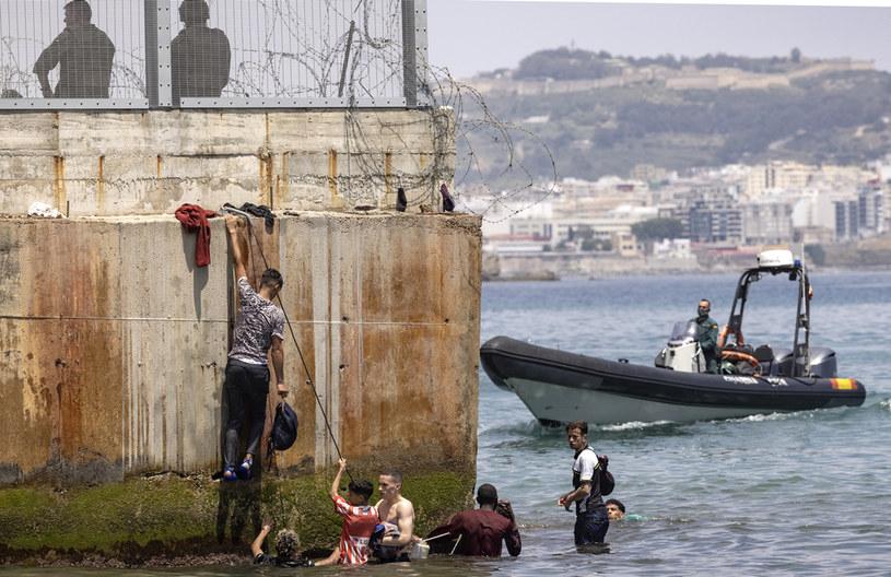 """""""To szokujący obraz - dzieci wskakujące do wody, całe rodziny i to wszystko przy współpracy służb marokańskich, które nawet wskazują, którędy najlepiej dotrzeć na terytorium Hiszpanii"""" – pisze """"El Mundo"""" /AFP"""