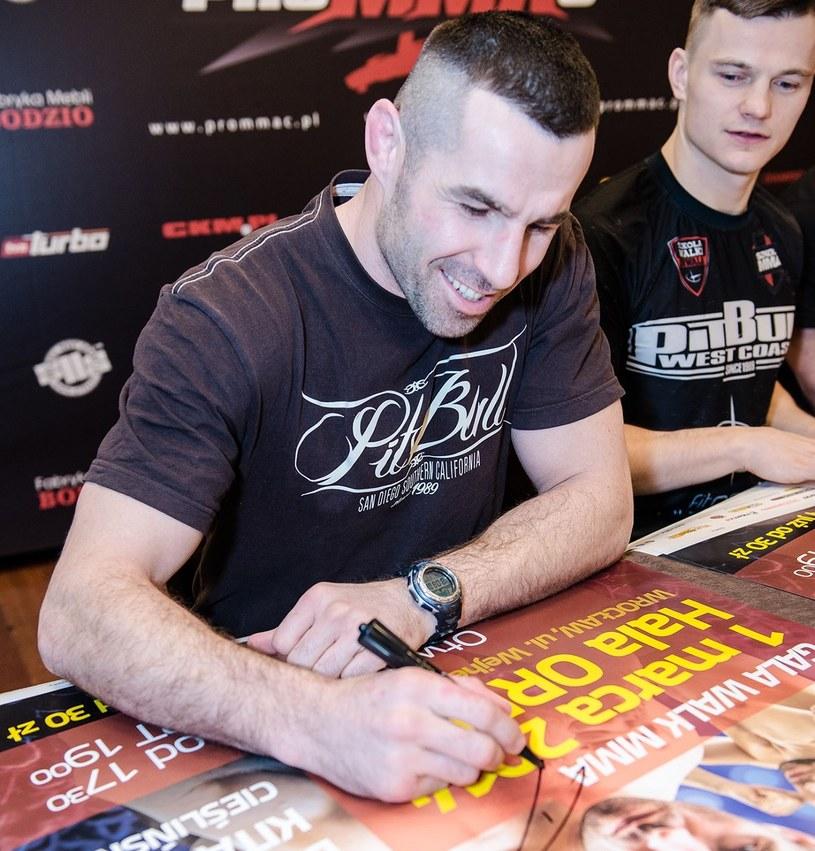 Tomasz Drwal i Damian Milewski podpisują plakaty przed PROMMAC 1 /INTERIA.PL